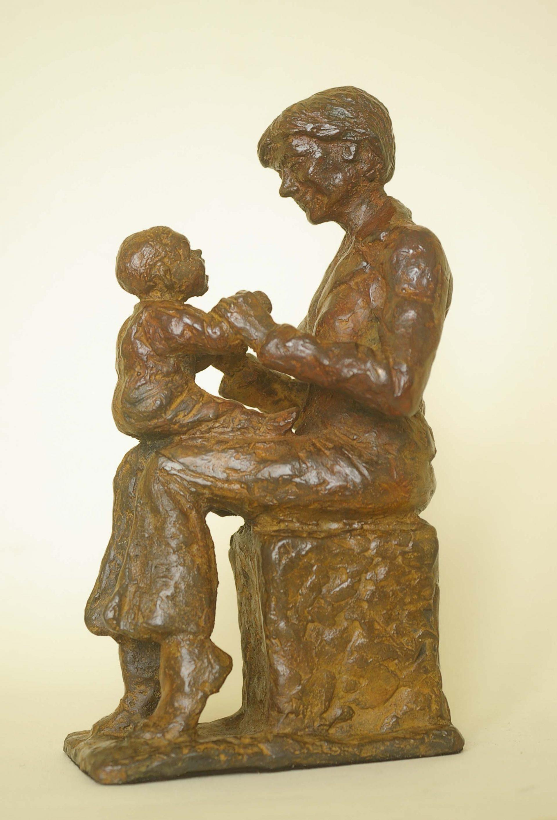 Bronzen beeld van Moeder met kind op schoot. Spelletje met kind, realisme